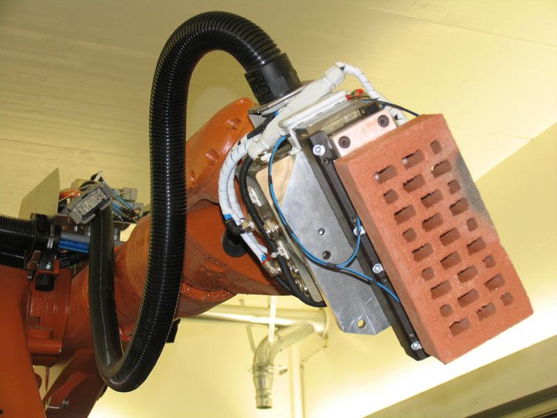 Ein eigens entwickelter Greifer erlaubt es dem Roboter Backsteine aufzunehmen.