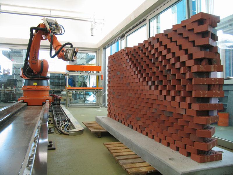 Produktion einer Backsteinwand. Ein eigens entwickelter Greifer erlaubt es dem Roboter die Steine aufzunehmen und im Raum zu positionieren.
