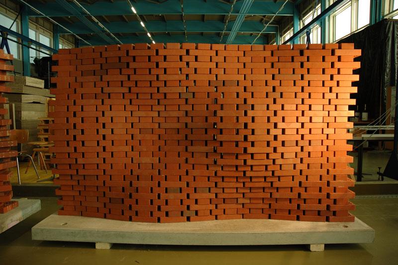 Die Wand wird verformt, indem Mulden in die Ebene hineingedrückt werden. Zur Gewährleistung der Standsicherheit erzeugt jede Bewegung nach innen eine Gegenbewegung nach aussen.