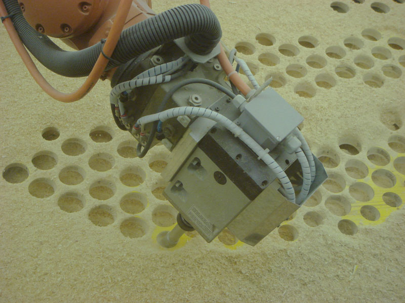 Das Fräsen der Schalungsbretter übernimmt der Industrieroboter. Er führt schnell und präzise die programmierte Perforierung aus.