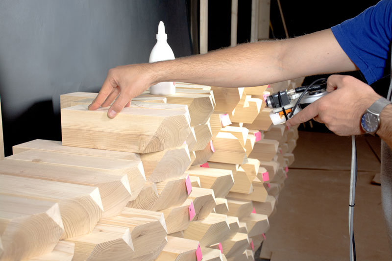 Builder placing one timber block with camera set-up